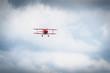 Leinwanddruck Bild - Vintage red propeller plane flying on a blue sky