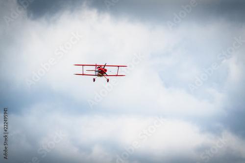 Leinwanddruck Bild Vintage red propeller plane flying on a blue sky