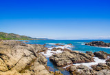 Beautiful view of beach with rock formations in the ocean with waves approaching and blue sky near sand and forest