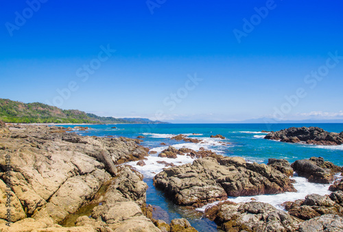 Foto Murales Beautiful view of beach with rock formations in the ocean with waves approaching and blue sky near sand and forest