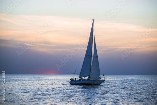 White yacht sails at sunset, Baltic sea, Latvia