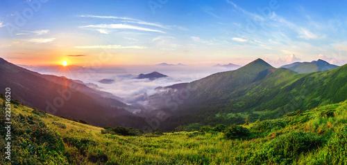 Leinwanddruck Bild Beautiful sunrise in mountains with white fog below panorama