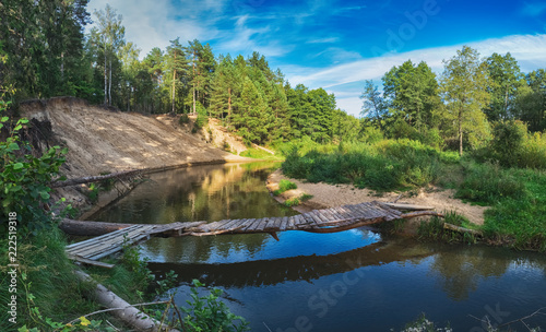 Fototapeta Beautiful Landscape Of Forest River With Bridge And Reflections Of Clouds And Trees Belarus