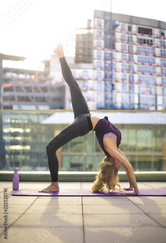 Wall mural Girl doing yoga exercises on a terrace