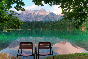 Vacant Chairs admiring fusine lakes reflection landscape italy