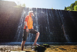 Young blonde man standing in front of a waterfall
