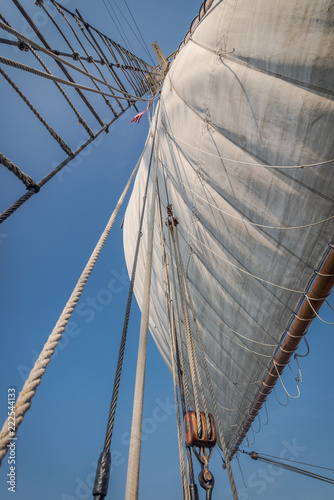 View looking up through the rigging to the top of the mast on a tall ship with white sails
