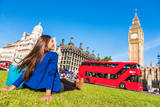 Fototapeta Big Ben - Happy tourist woman relaxing in London city at Westminster Big ben and red bus. Europe destination travel lifestyl.e © Maridav