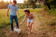 Young couple walking pug dog in autumn forest. Happy puppy running along and having fun playing with masters. - 222549332