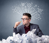 Young businessman sitting behind crumpled paper with drawings of gears and steam over his head - 222552524