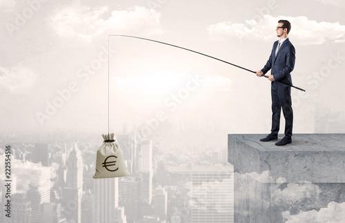 Leinwandbild Motiv Businessman fishing sack of currency from the cityscape concept