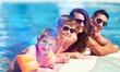 Leinwandbild Motiv Happy family playing in swimming pool