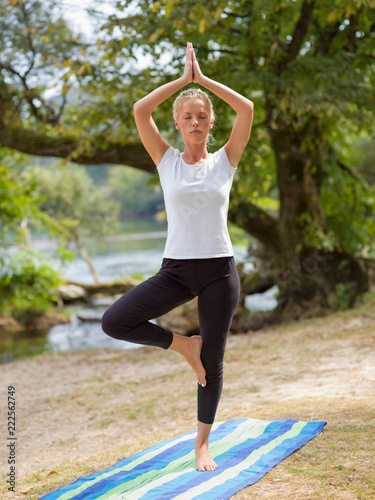 woman meditating and doing yoga exercise - 222562749