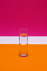 Glass with a glass of liquid on a colored background