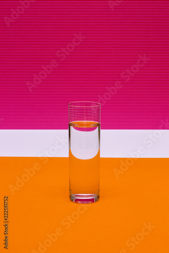Glass with a glass of liquid on a colored background - 222581752
