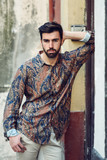 Young bearded man, model of fashion, wearing shirt in urban background. - 222589100