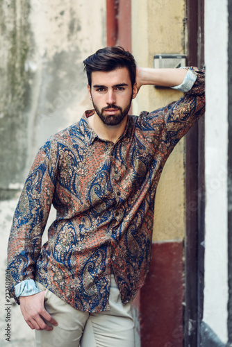 Poster Young bearded man, model of fashion, wearing shirt in urban background.