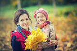Smiling little girl and her mother enjoy walk in autumn park and play with bright autumn leaves - 222589715