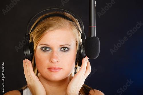 Fototapeta Woman singing to microphone wearing headphones in studio