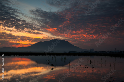 Dramatic sunrise with beautiful cloud over a hill with reflection in the foreground