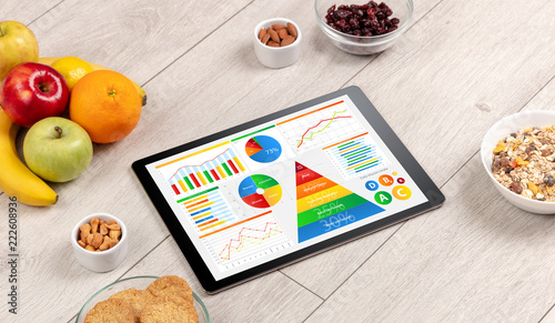 Leinwandbild Motiv healthy eating concept - close up of tablet with several dieting statistics