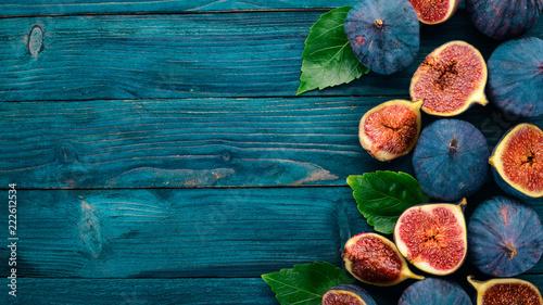 Fig. Świeże figi owocowe na niebieskim drewnianym stole. Wolne miejsce na tekst. Widok z góry.