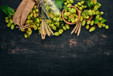 Hops and wheat. On a black wooden table. Free space for text. Top view. - 222613383