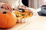 Adult woman in the kitchen preparing pumpkin dishes for Halloween - 222616193