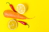 Carrots, red peppers and lemon halves on yellow background.
