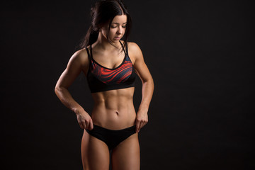 Sporty girl with ripped abdominal muscles in black sportswear. Tanned young sexy athletic fitness instructor isolated over black background with copyspace. © alfa27