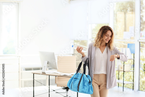 Leinwanddruck Bild Young beautiful businesswoman holding fitness bag in office. Space for text