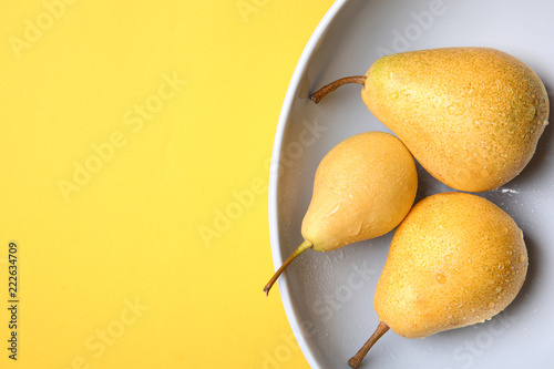 Leinwandbild Motiv Plate with ripe pears on color background, top view. Space for text