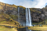 Seljalandsfoss, Iceland - Oct 22th 2017 - Tourists enjoying the Seljalandsfoss fall in a overcast day in Iceland.
