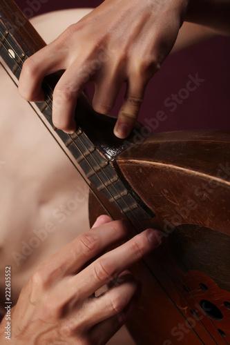 Fototapeta Man's hands with folk musical instrument domra