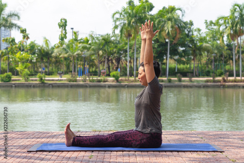 healthy middle aged asian woman sitting and raise arms to start paschimottanasana yoga pose in city park at the morning. healthy and lifestyle concept.