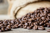 Fresh roasted coffee beans on rustic wood background