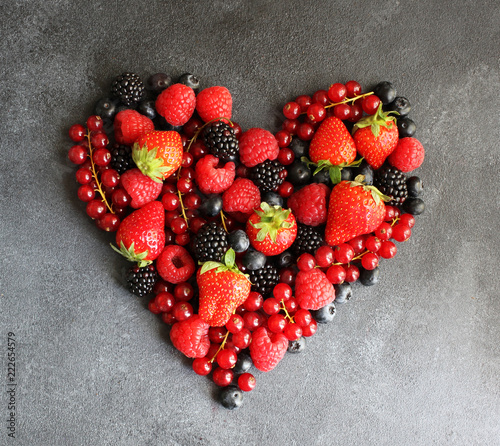 Heart of fresh berries on dark board, top view - 222654579