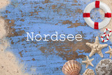 Maritime Dekoration auf blauem Holzuntergrund und die Beschriftung
