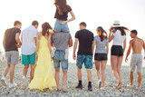 happy young mans and womans walk at the beach. Group of friends enjoying beach holidays