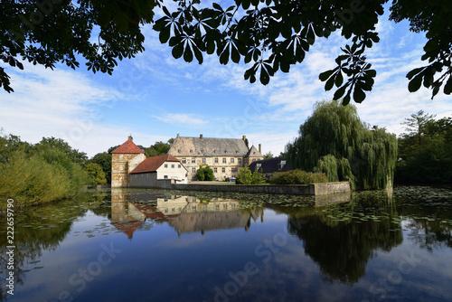 Leinwanddruck Bild Wasserschloss Tatenhausen mit blauem Himmel und Wolken, NRW, Deutschland, Water castle Tatenhausen with blue sky and clouds, Germany