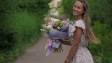 Girl holding a bouquet of fresh flowers in her hands - 222662985