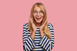 Excited happy impressed girl clasps hands near face, notices something thrilling, dressed in casual striped sweater, expresses positive emotions, stands alone against pink background. Wow, its cool!