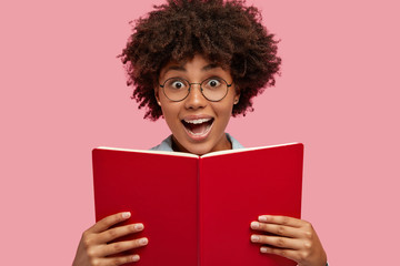 Photo of amazed dark skinned woman has satisfied expression, holds red book near face, feels excited with thrilling story, looks surprisingly through spectacles, isolated over pink background