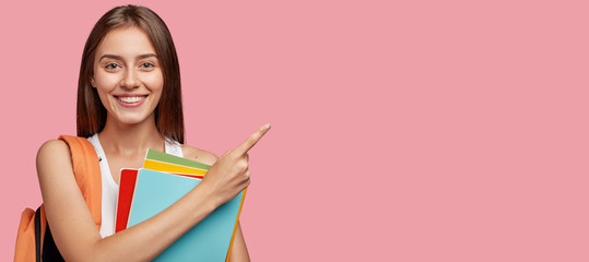Studio shot of positive Caucasian woman with shining smile, dark straight hair, poins at upper right corner, shows free space for your advertisement, ready for school, isolated over pink background