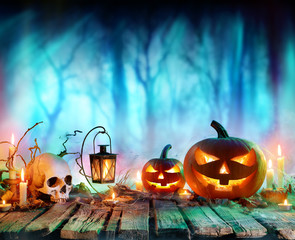 Jack O' Lanterns And Candles On Table In Misty Forest - Halloween Background