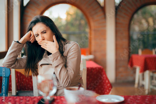 Sleepy Woman Yawning while Waiting In a Restaurant