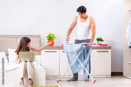 Man ironing, his lazy wife sitting  - 222728122