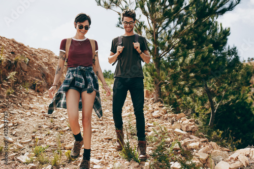 Couple wearing backpacks hiking in the countryside