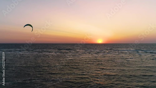 Silhouette of kiter in the sea at sunset time, aerial view