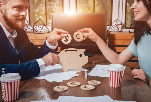 A businessman with a bank employee holds a coins under a wooden pig. Money box. Collecting money with earning bank. - 222763995